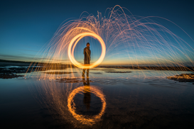 EyeEm Foto's bijv. als canvasfoto of wandfoto achter acrylglas: Man Spinning Wire Wool While Standing At Sea Shore Against Sky