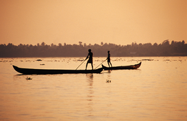 Foto: Reis om de wereld - Two men poling canoes on Vembanad Lake.