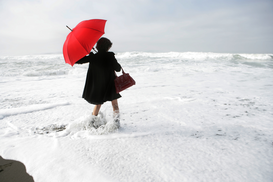 Staged photography Wall Art as Canvas, Acrylic or Metal Print Woman with red umbrella standing in the sea.