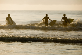 Foto: Watersport - Surfer dudes and girl running into surf with surfboards