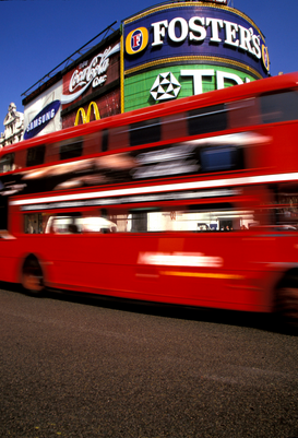 Foto: Londen - A red double decker bus passing a Fosters sign in Piccadilly Circus, London, England.