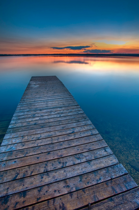Strandbilder z.B als Leinwandbild oder Wandbild hinter Acrylglas: Sunset over a wooden wharf on Lake Audy, Riding Mountain National Park, Manitoba, Canada