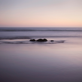 Foto: Aan zee - Rock in sea at sunset